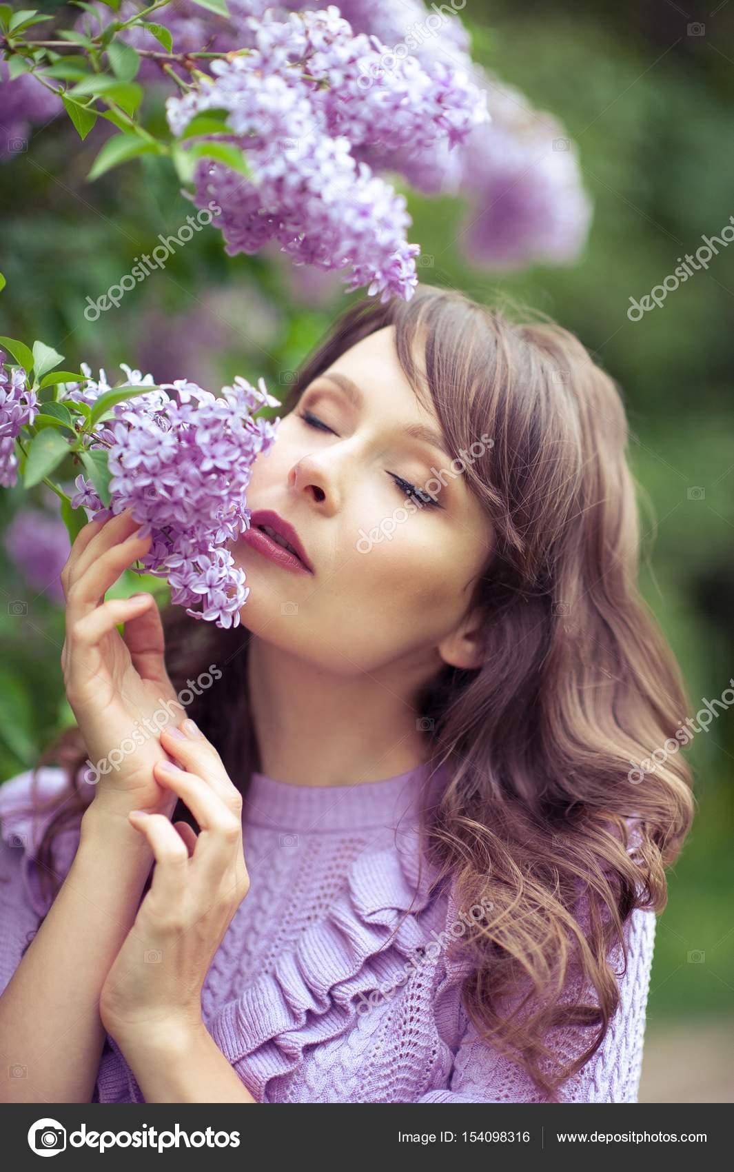 61d75905f8 Młoda kobieta piękne spacery wzdłuż ogród wiosną. Dziewczynka stoi w  pobliżu bzy. Liliowy. Kwiaty– obraz stockowy