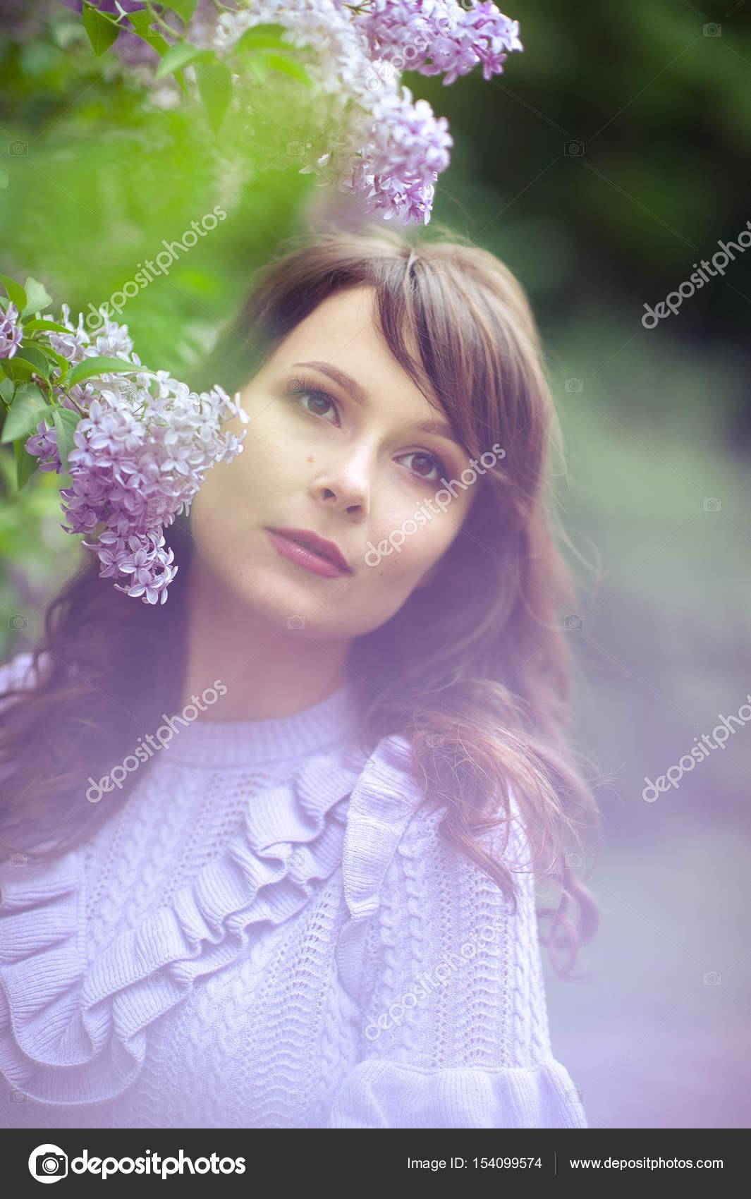 Joven mujer hermosa pasea por el jardín de primavera. Una chica se ...