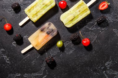 Photo on top of frozen fruit ice on sticks and berries on empty black background