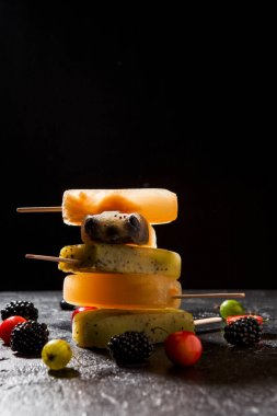 Photo on top of frozen fruit ice on each other and berries on empty black background