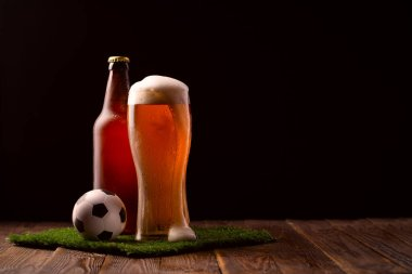 Photo of buttle and glass of beer, soccer ball on green grass at table stock vector