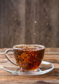 Foto bylinný čaj v šálku na hnědém pozadí