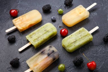 Photo of frozen fruit juice on sticks and berries on empty black background
