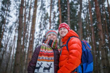 Image of happy couple on walk in winter forest against background of trees