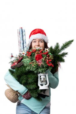 Photo of woman in Santa's cap with Christmas tree, lantern, wrapping paper in hands on empty white background