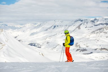 Photo of sportive man skiing against background of snowy mountains during day