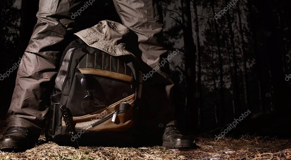 Фотообои Man in tactical outfit standing over a backpack with camping and tactical gear on night forest background.