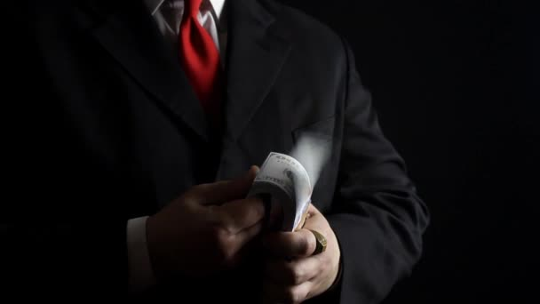Rich businessman holding money. Photo of a rich businessman in black siut with red tie holding and counting money pack.