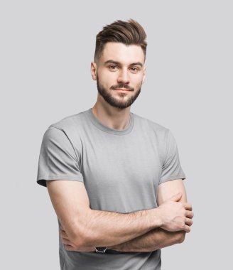 Portrait of handsome smiling young man with folded arms. Smiling joyful cheerful men with crossed hands studio shot. Isolated on gray background stock vector