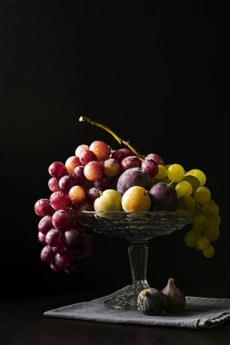 Autumn fruits on a glass fruit platter on a black napkin with a black background