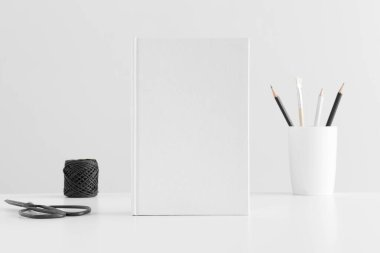 White book mockup with workspace accessories on a white table.