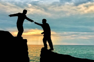 Climber helps friend in mountains of giving helping hand over precipice