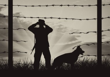 Hole in fence on border and border guards with dog
