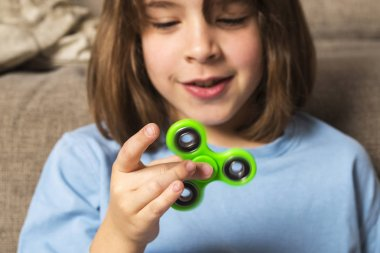 Little girl playing with green fidget spinner toy