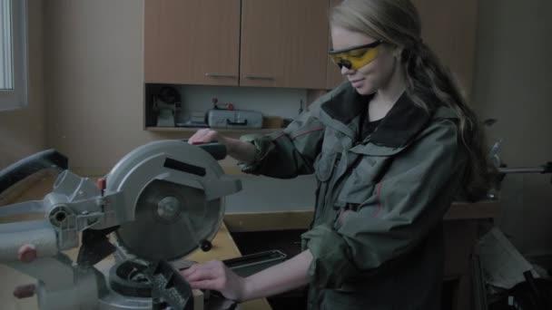 Mädchen in einer Werkstatt sägt Holzmaterialien und lächelt