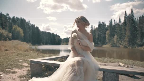 Blondes Mädchen in weißem Kleid am See