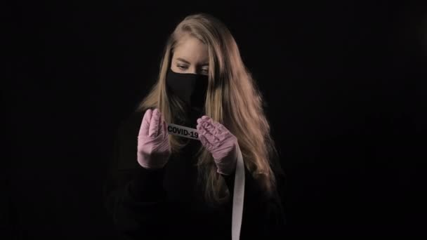 Girl in a black mask holds a ribbon with the inscription covid-19. Isolated on black background. Health care and medical concept. Close up portrait . 4k. Coronavirus Epidemic, illness, pandemic