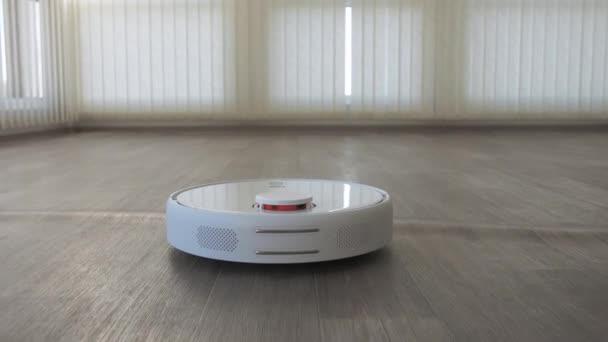 Weißer Staubsaugerroboter auf Linoleum-Holzboden