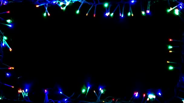 Garland flickering blue, red, green on a black background. A multi-colored garland is lined with a rectangle around the perimeter of the frame. Frame of garland. Christmas background.