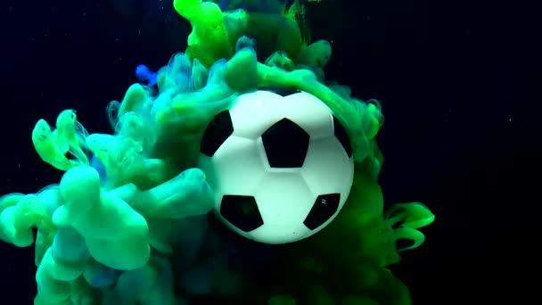 Focilabda csodálatos háttérrel. Zöld és kék tinta vízben, fekete háttérrel. Fogalom a reklám futball verseny. Egy fantasztikus képernyővédő..