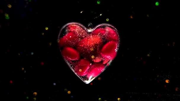Úžasné srdce plné malých šarlatových srdcí se točí na černém pozadí. Koncept na Valentýna 14. února. Krásné slavnostní pozadí s barevným bokeh.