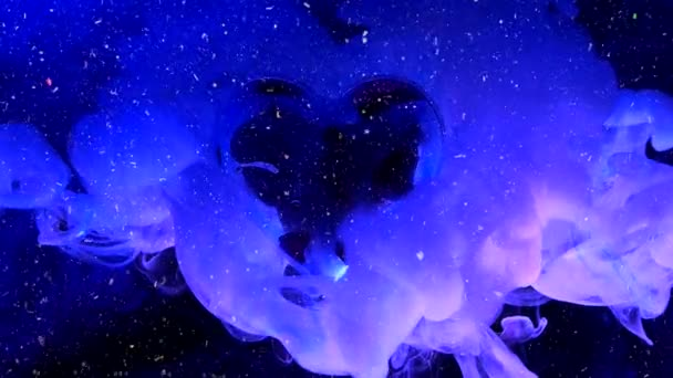 schönes Herz in blauem und violettem Rauch auf dunkelblauem Hintergrund. Konzept für den Valentinstag am 14. Februar. schöner festlicher Schnee Hintergrund mit Funkeln.