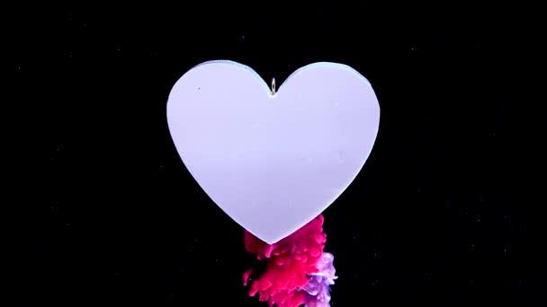 Zpomalit video velké bílé srdce na krásném šarlatovém pozadí. Koncept na Valentýna 14. února. šarlatové a růžové inkoust ve vodě na černém pozadí.