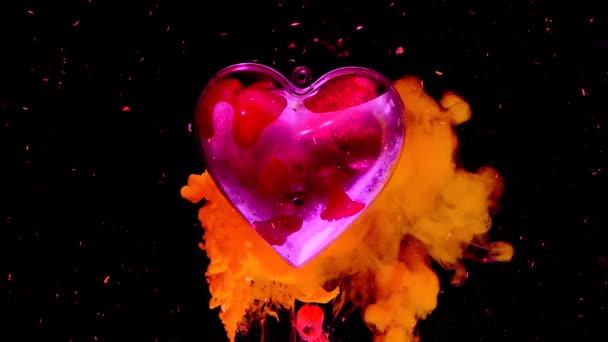Šarlatové srdce na zářivém ohnivém pozadí. Koncept na Valentýna 14. února. Žlutý a červený inkoust ve vodě na černém pozadí.