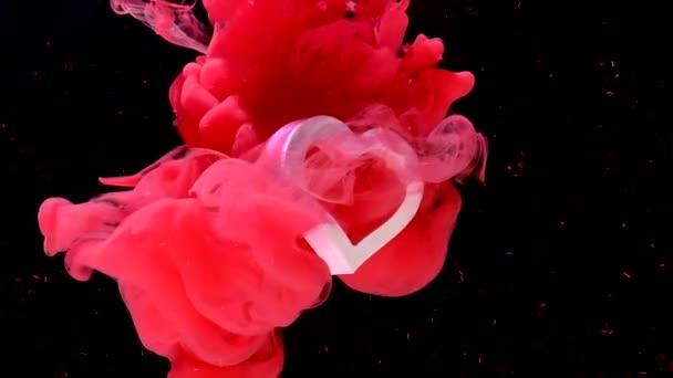 weißes Herz dreht sich um seine Achse auf einem schönen roten Hintergrund mit glänzenden Funkeln. Konzept für den Valentinstag am 14. Februar. rosa Tinte im Wasser auf schwarzem Hintergrund.