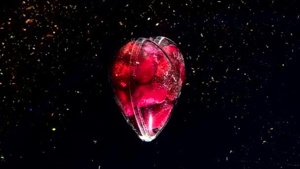 Lesklé skleněné srdce naplněné malými červenými srdíčky se otáčí kolem své osy. Koncept na Valentýna 14. února. Krásné slavnostní pozadí se zlatými jiskry.
