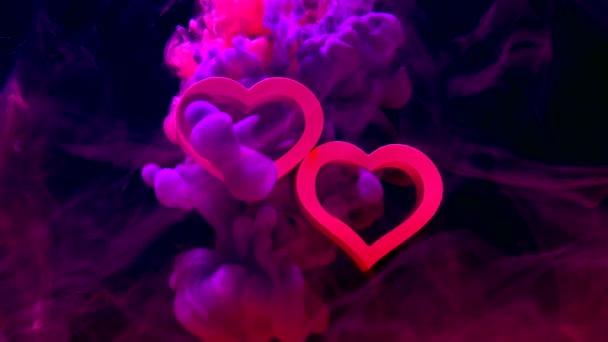 Két rózsaszín szív egy csodálatos kozmikus háttérrel. Fogantatás Valentin-napra február 14-én. Violet és orgona tinta vízben sötét kék alapon.