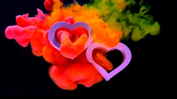 zwei schöne weiße Herzen auf einem fantastischen Raumhintergrund. Konzept für den Valentinstag am 14. Februar. gelbe, orange und rosa Tinte in Wasser auf schwarzem Hintergrund.