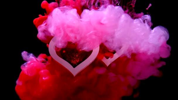zwei schöne Herzen auf einem schönen rot-rosa Hintergrund. Konzept für den Valentinstag am 14. Februar. rote Tinte im Wasser auf schwarzem Hintergrund.