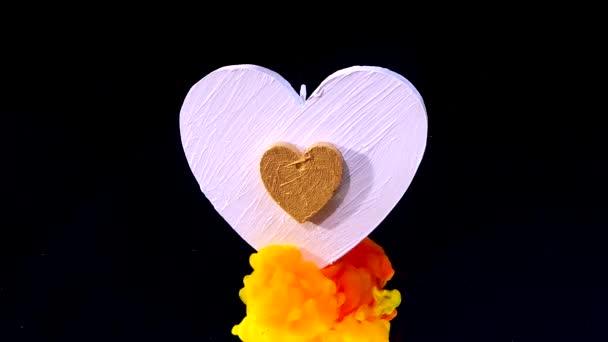 Zpomalte pohyb bílého dřevěného srdce se zlatým srdcem uprostřed na ohnivém pozadí. Koncept na Valentýna 14. února. Žlutý a oranžový inkoust ve vodě na černém pozadí.