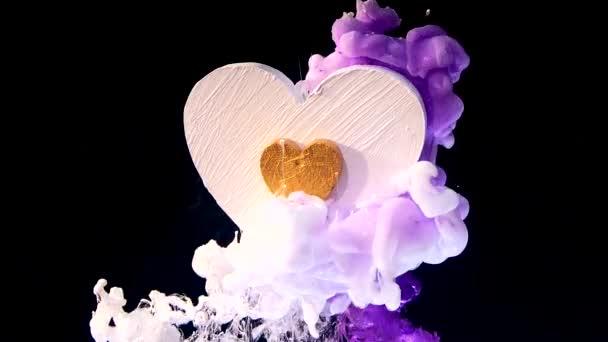 weißes Holzherz mit goldenem Herzen in der Mitte auf schönem Hintergrund. Konzept für den Valentinstag am 14. Februar. weiße und violette Tinte in Wasser auf schwarzem Hintergrund.