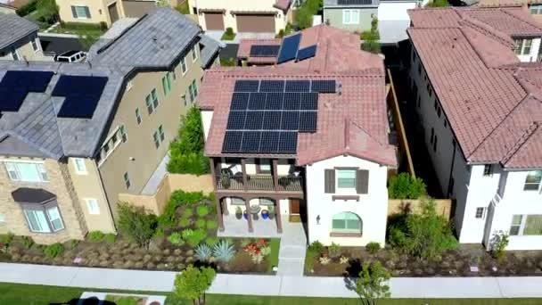 Vzdušný pohled stoupá táhnout zpět nad obytné domy s technologií solárních panelů na předměstských střechách