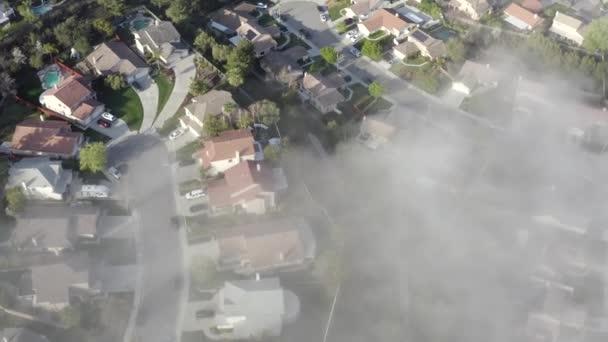 Aerial birds eye over morning fog of neighborhood homes