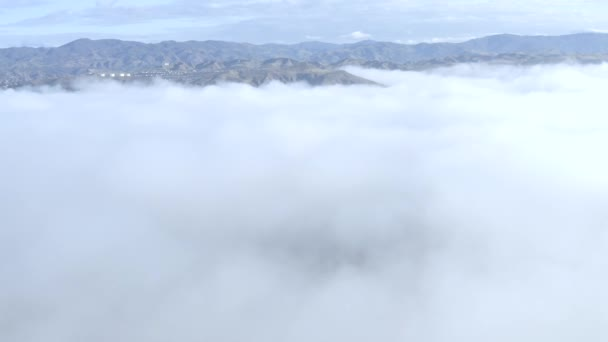 Letecký oblak sestup, hory pokryté ranní mlhou, odhalující okolí domů, Los Angeles
