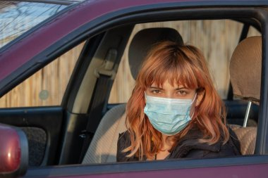 Girl wearing medical mask in the car. Woman wearing mask, written COVID-19, to protect from corona virus. Driving car with mask during virus pandemic. Mask must be put on in everyday activities.