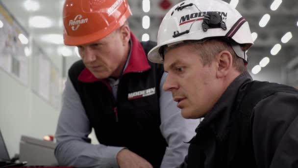 Magadan, Rusko - 15. srpna2019. Továrna na obnovu motorů a převodovek pro těžká zařízení. Dva dělníci u počítače. Připravují se nastartovat motor..