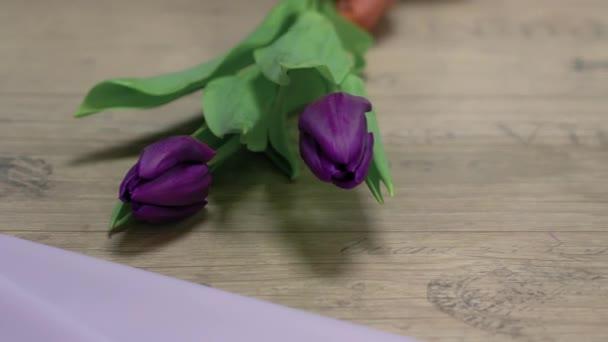 Květinářství sbírá kytici fialových tulipánů.