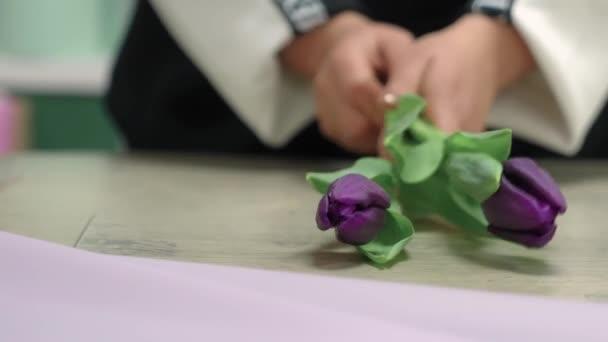 A virágárus összegyűjt egy csokor lila tulipánt..