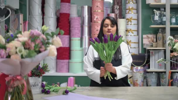The florist looks at a bouquet of flowers and adds a purple tulip.