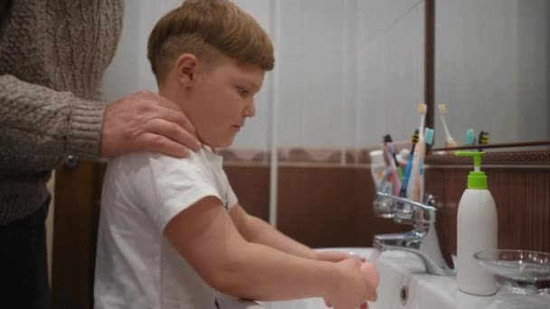 Enkel wäscht sich im Badezimmer die Hände Opa hilft ihm.