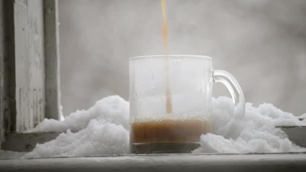 Man gießt heißen Kaffee mit Milch in einen Glaskrug