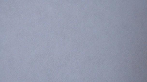Flüssige Farbe ist auf einem weißen Papier mit einem Pinsel aufgetragen.