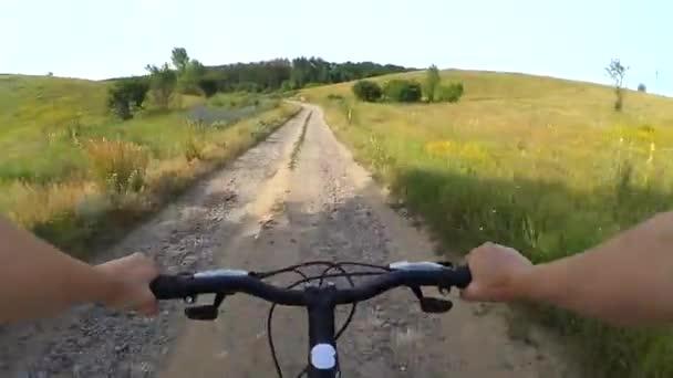 Cyklistika na prašné cestě země v zeleném poli