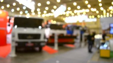Many cars trucks lorry inside the exhibition pavilion and people walk around