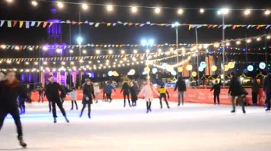 Ice rink with many people outdoors open by night.
