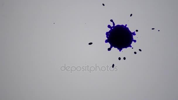 violette Tinte Tropfen Tropfen auf die weiße Fläche